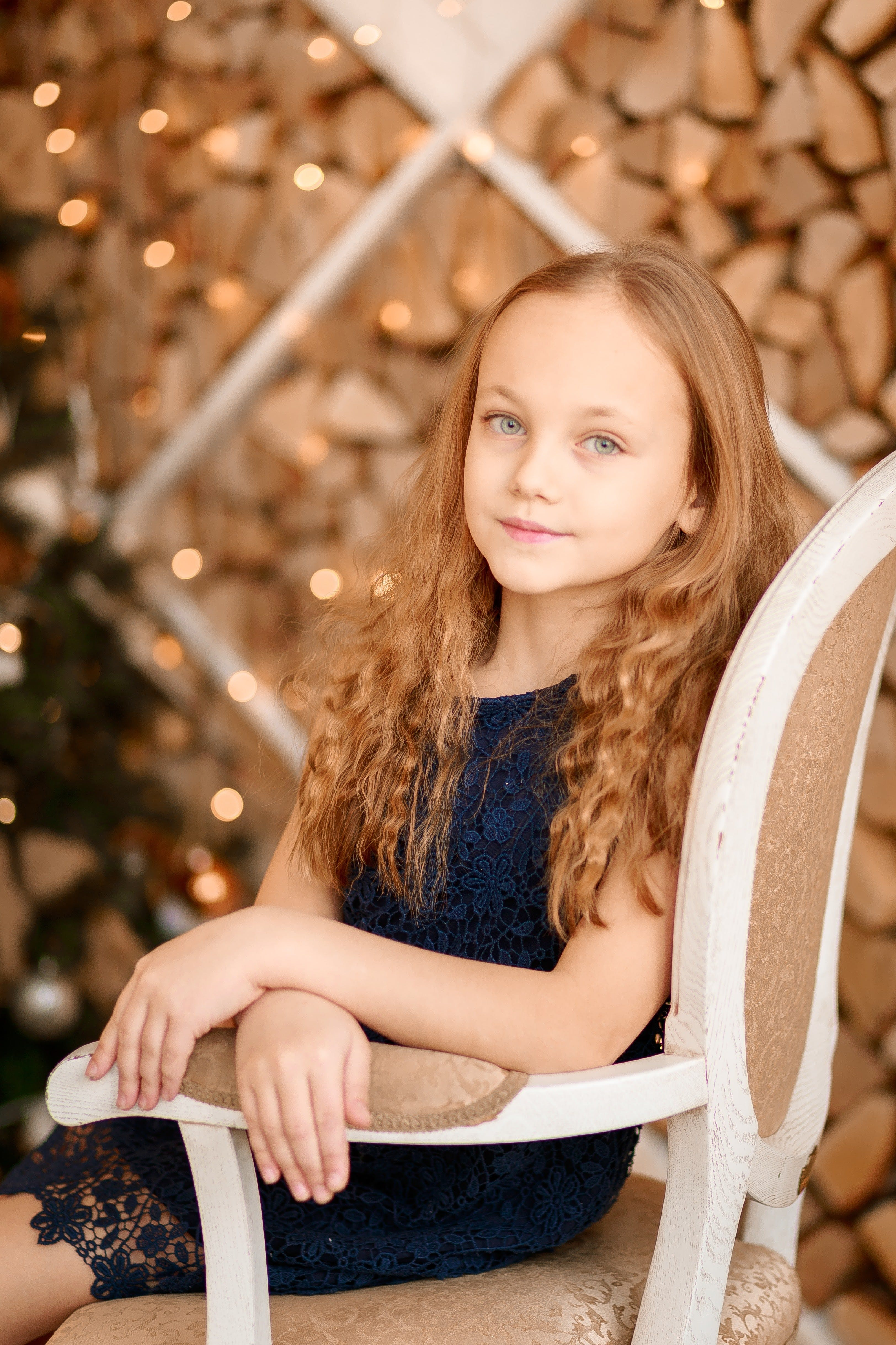 Girl Sitting on White and Brown Chair
