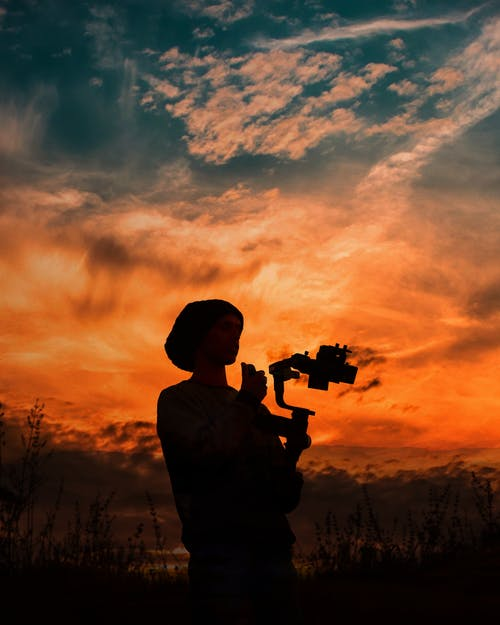 Silhouette of Person Holding Camera While Standing Under Orange and Blue Sky
