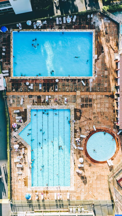 Aerial Photography of People on Rectangular and Circular Swimming Pool