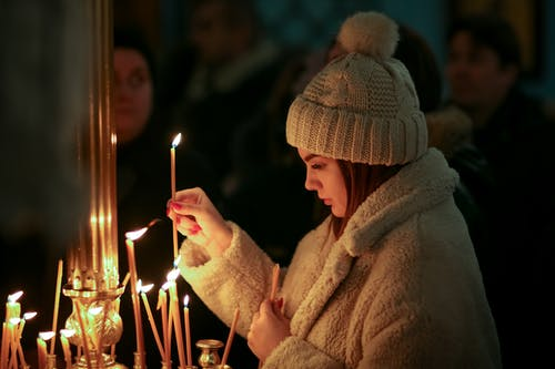 Woman in Brown Fur Coat and Cap Holding Lighted Candles