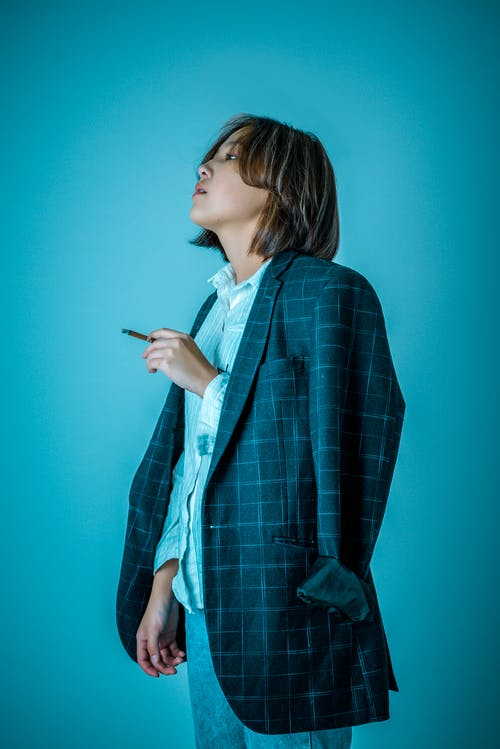 Woman Wearing Blazer While Standing Against Blue Background