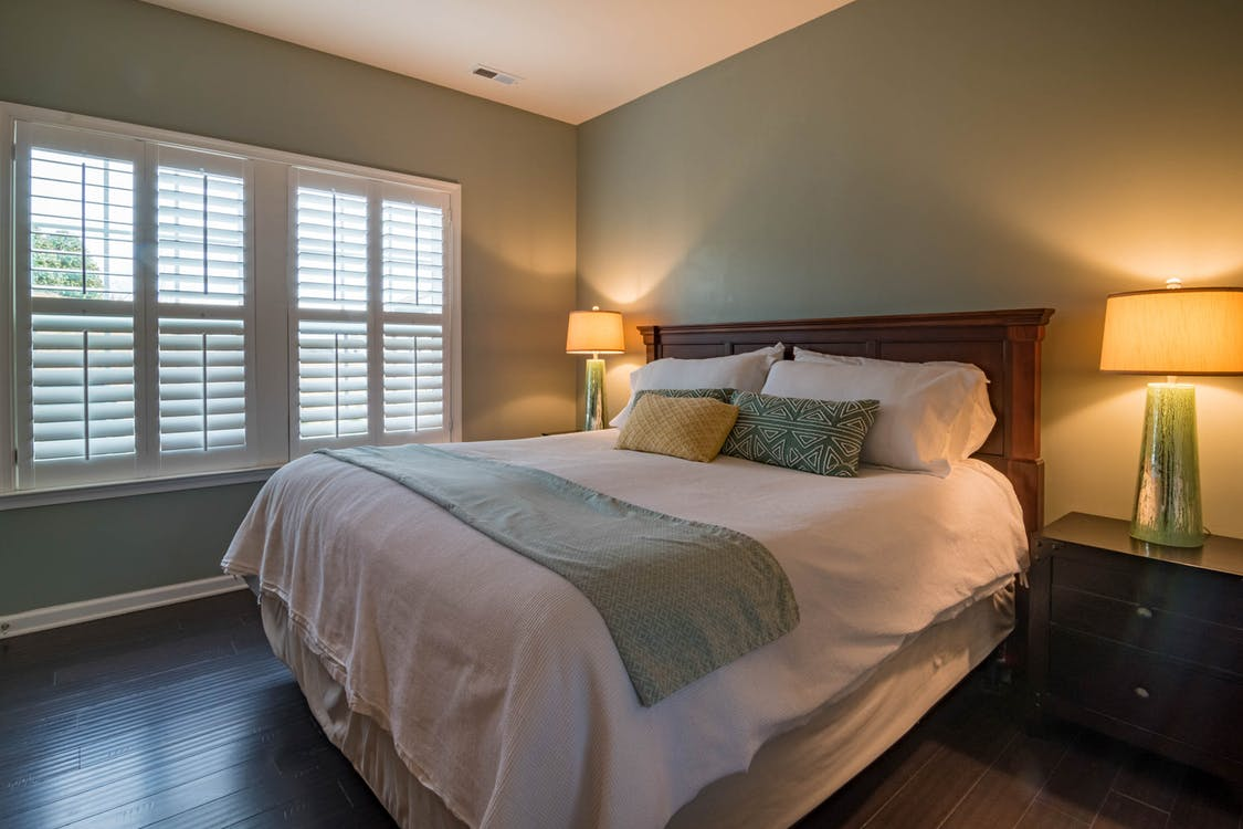 Bed Near Window Blinds and Lighted Desk Lamps