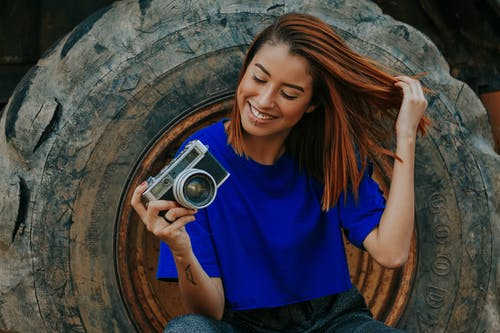 Shallow Focus Photo of Woman in Blue T-shirt Holding Camera