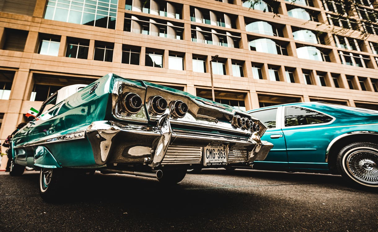 Green Vintage Car Parked Beside Brown Building