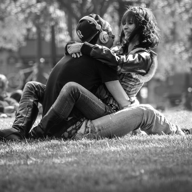 Grayscale Photo of Man and Woman Hugging on Grass