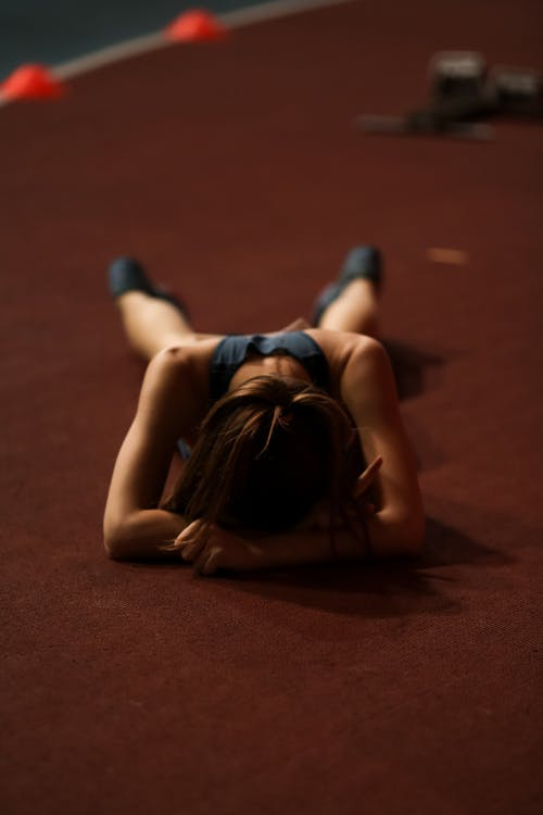 Exhausted young female runner in sportswear lying face down in stadium after running long distance