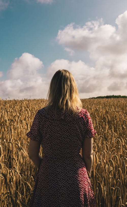 Woman Standing On Wheat Field