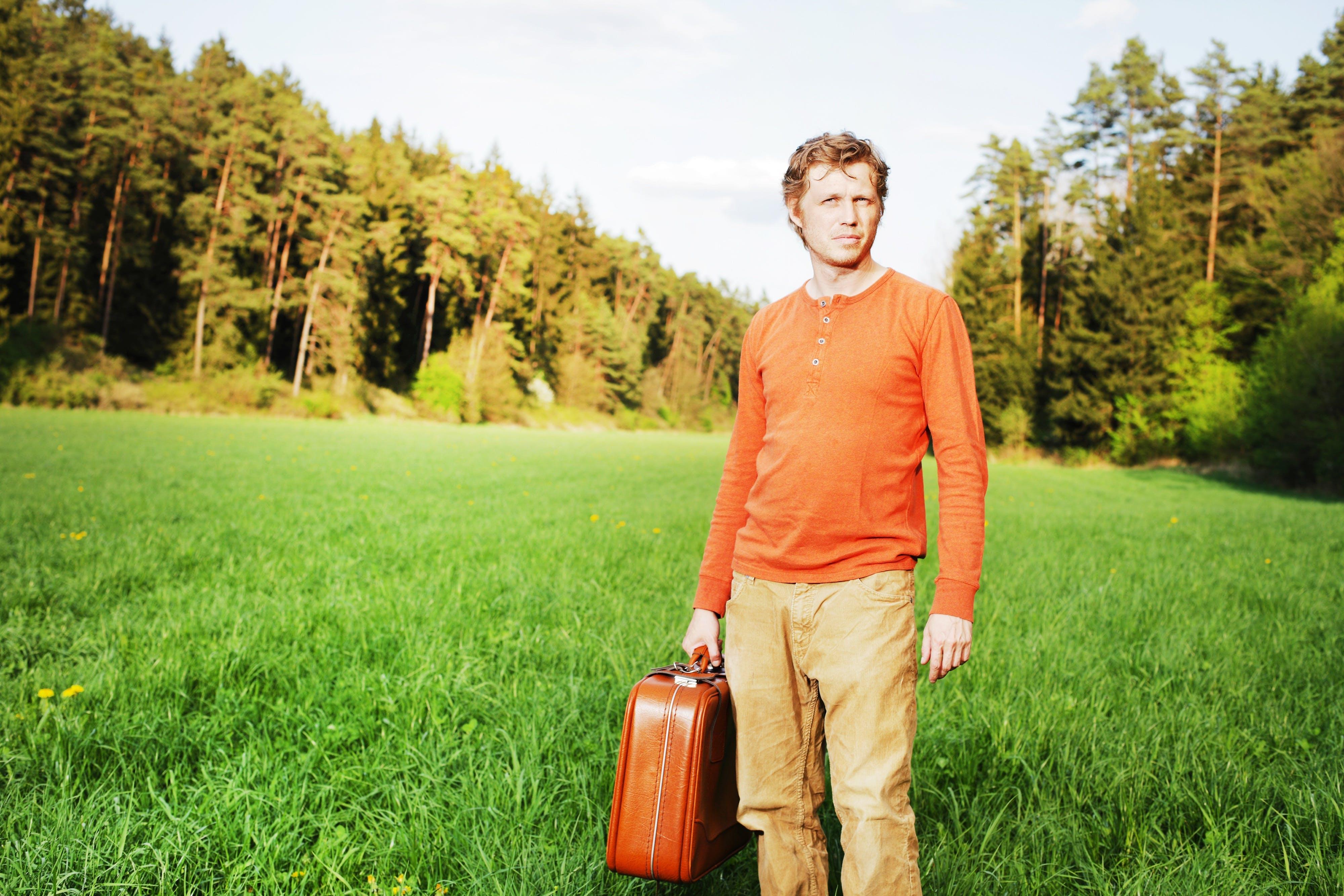 Man in Orange Henley-neckline Shirt Holding Suitcase