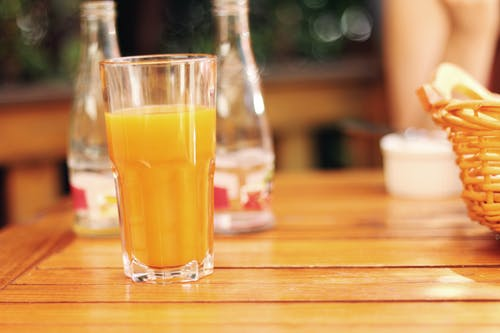 Clear Drinking Glass Filled With Yellow Liquid
