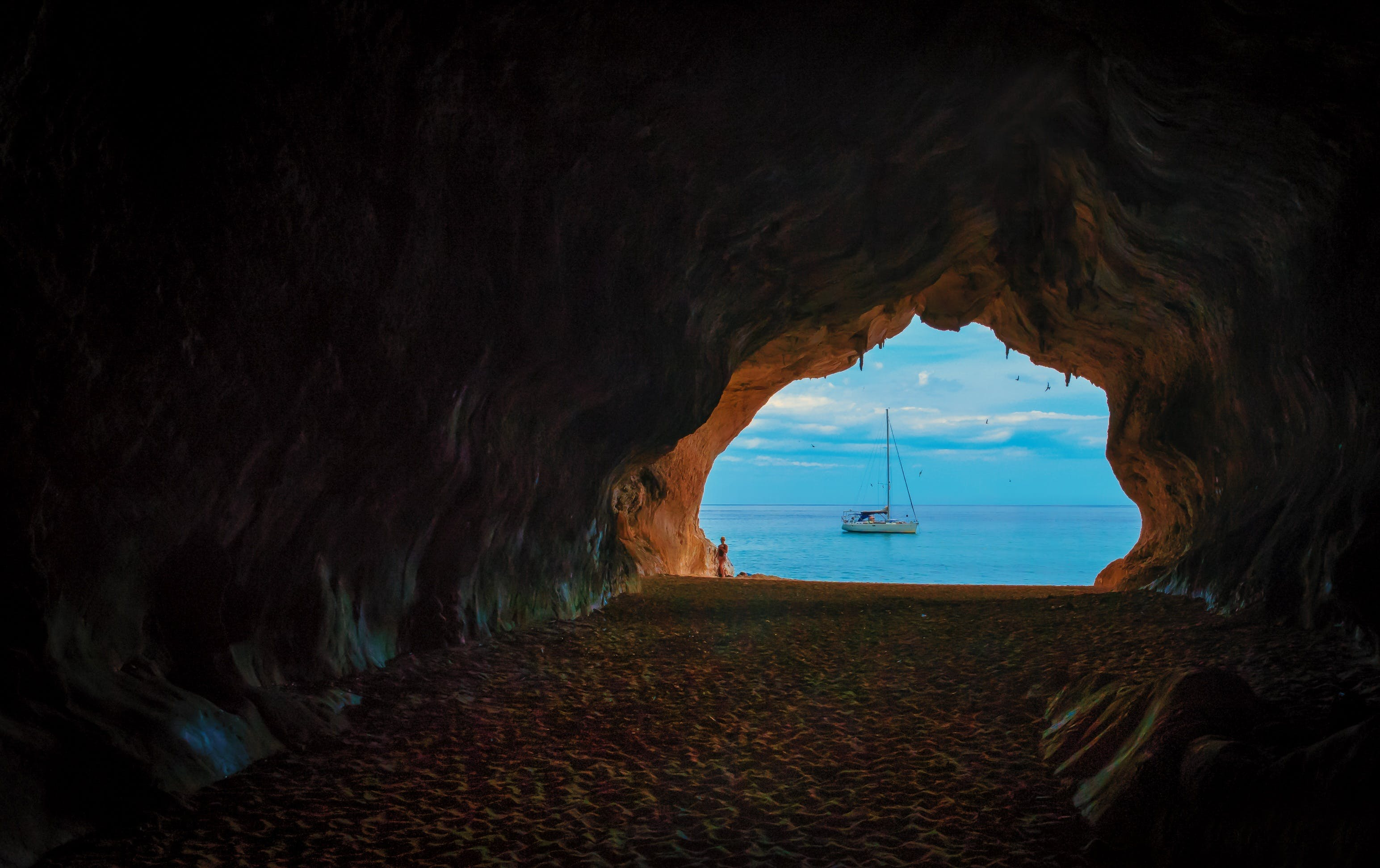 Cave Near Body of Water With Boat