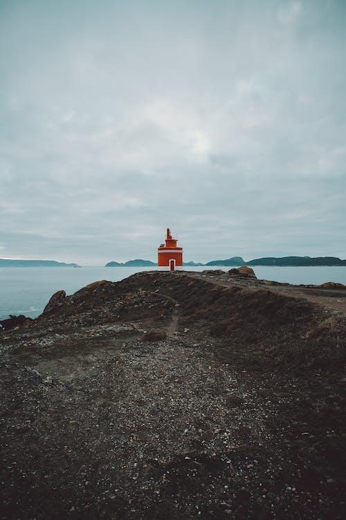 Lighthouse Near Sea Under Cloudy Sky
