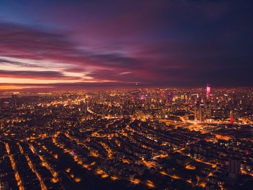Aerial view of modern city with glowing buildings located in downtown at night time with dark cloudy sky