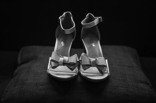 Grayscale Photography of Pair of Open-toe Ankle-strap Bow Accent Sandals