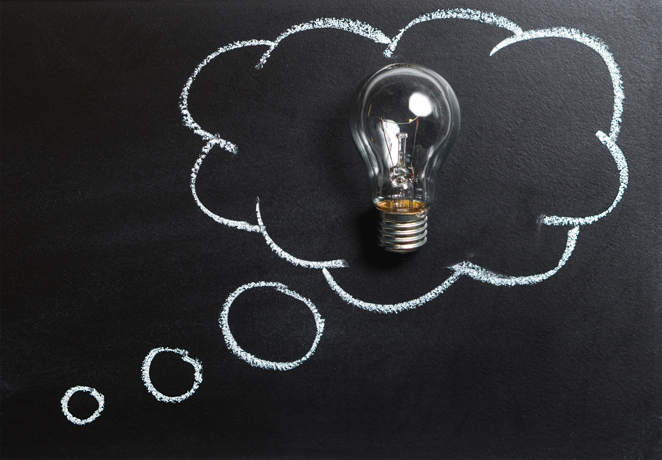clear light bulb placed on chalkboard free stock photo