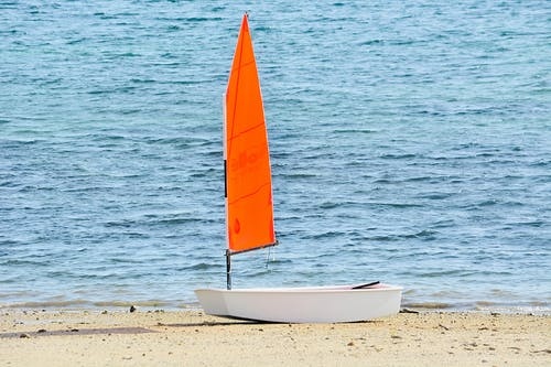 White and Orange Boat Near Body of Water