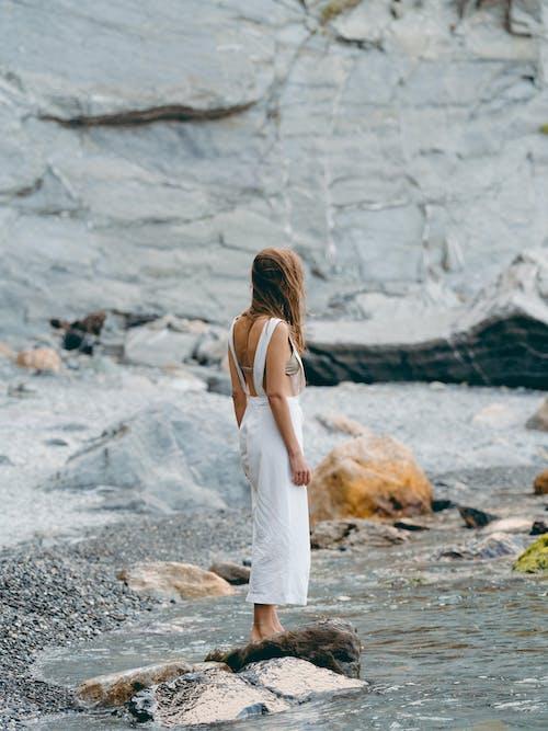 Woman in White Tank Dress Standing on Rock Near Body of Water