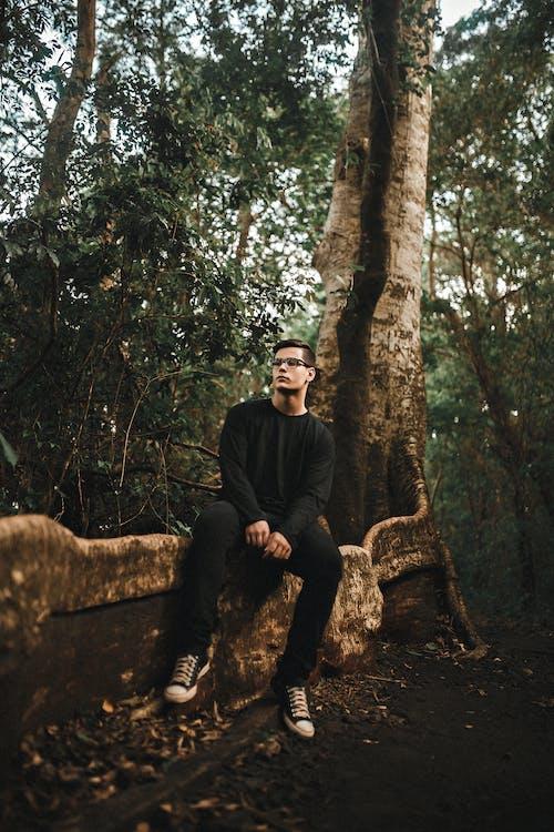Man Sitting on Tree Root