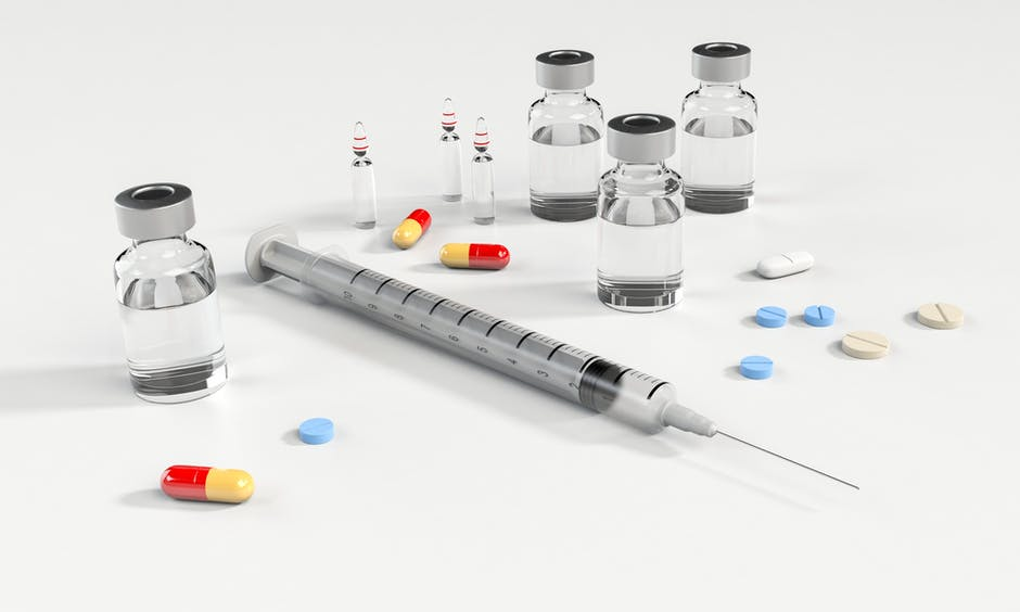 Syringe and Glass Bottle Beside Pills