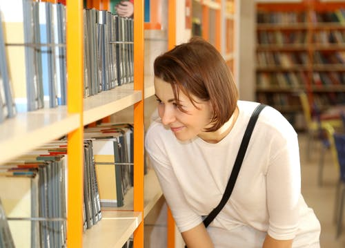 Woman Looking a Book on Shelf