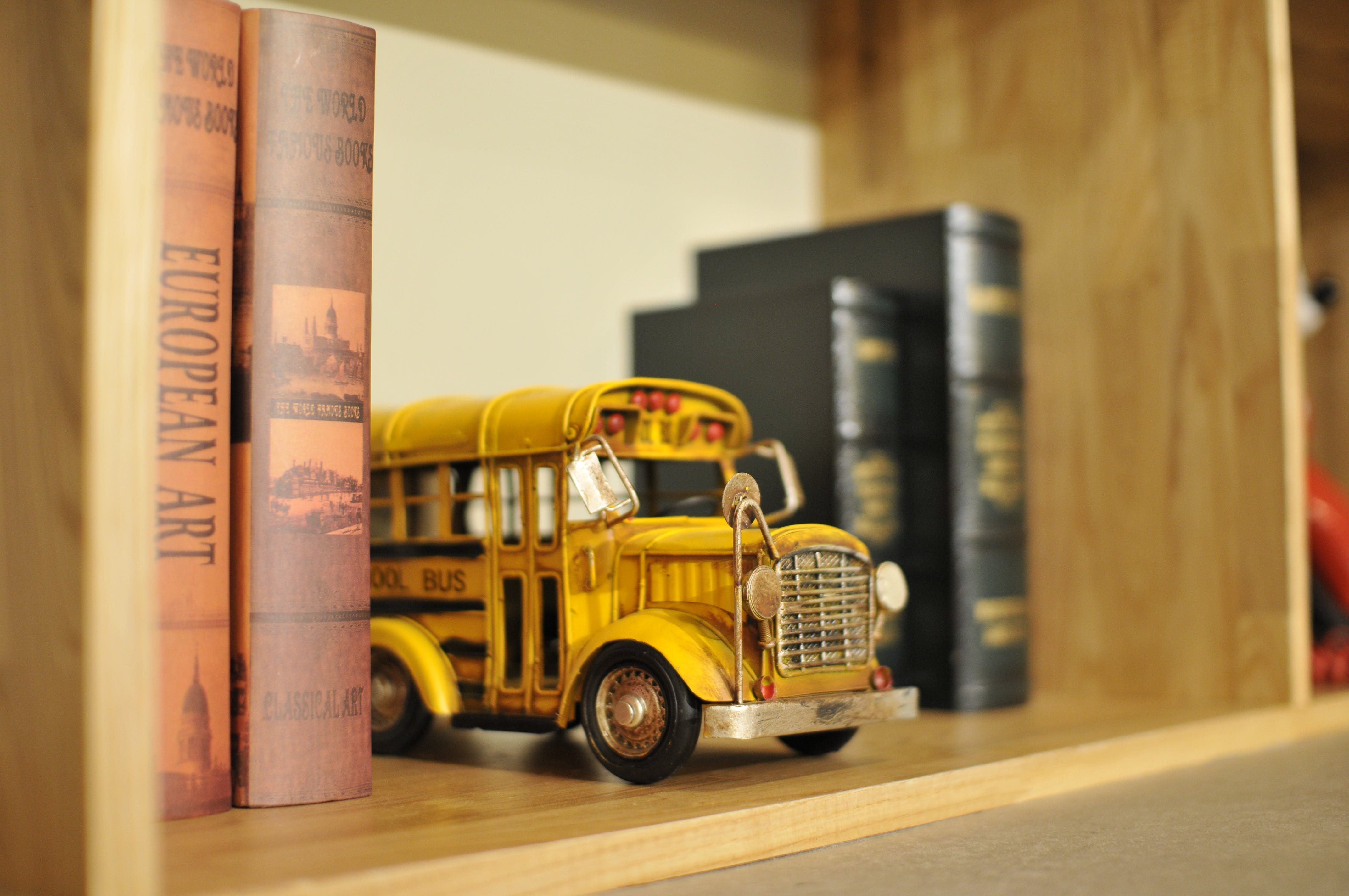 Yellow Bus Die-cast Model on Shelf Between Books