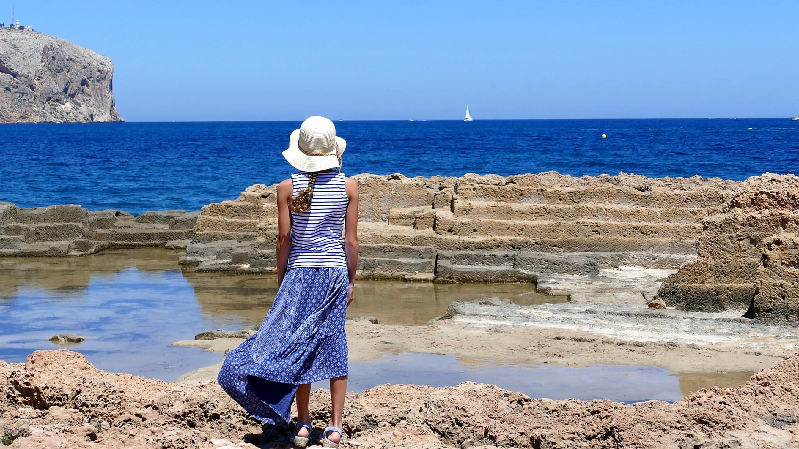 Woman in White and Blue Dress Near Sea