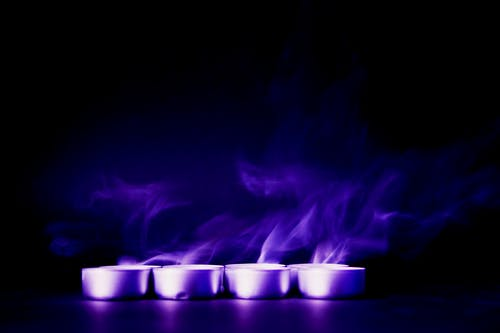 Four Tealight Candles With Purple Background