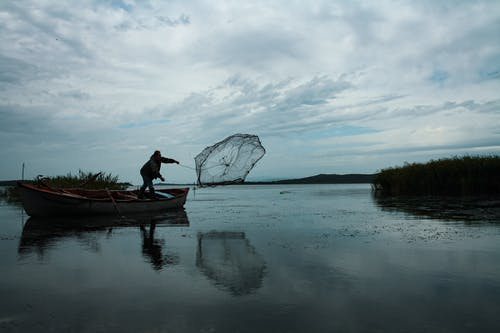Person Standing on Boat Trowing a Fishing Net into Body of Water