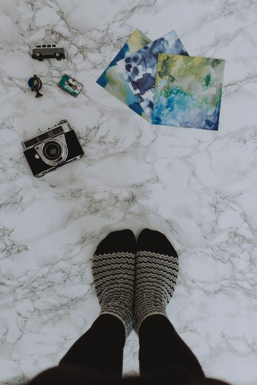 Gray and Black Camera Near Person's Feet Wearing Striped Socks
