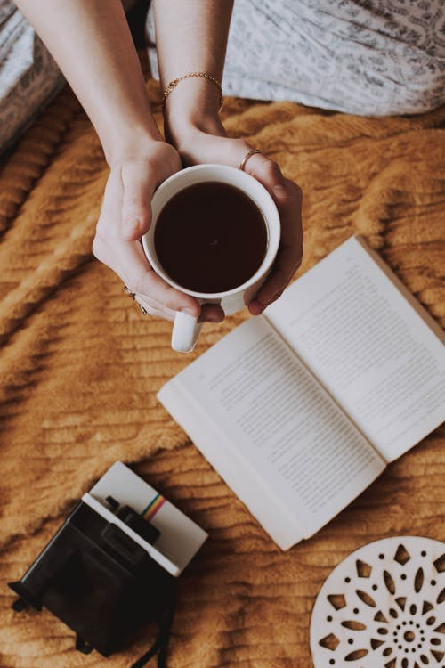 Woman Holding Mug of Coffee Beside Opened Book