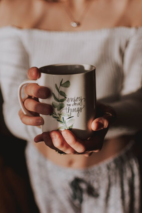 Person Holding White and Green Mug