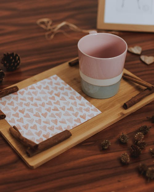 Pink, White, and Gray Ceramic Mug on Wooden Cutting Board