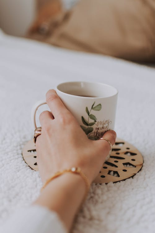 White and Green Mug on Brown Cutout Mat