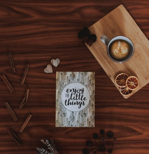 Enjoy Little Things Quote Card on Brown Wooden Surface