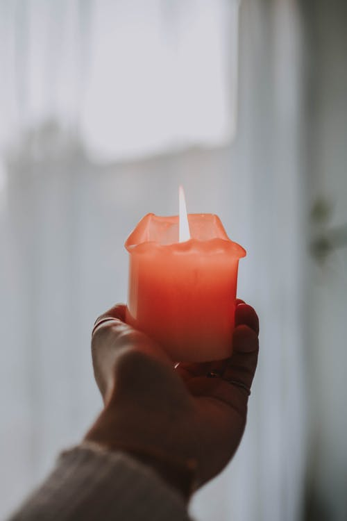 Person Holding Lighted Orange Candle