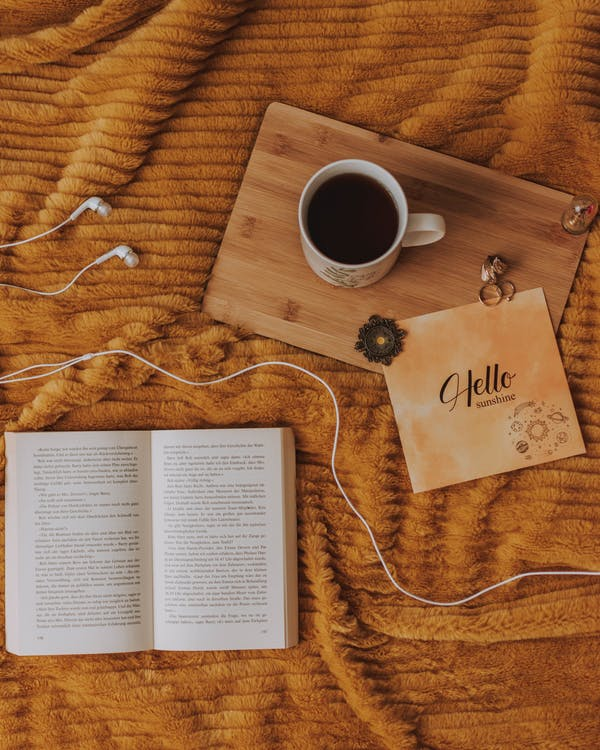 Full Mug on Wooden Cutting Board and White Book Pages
