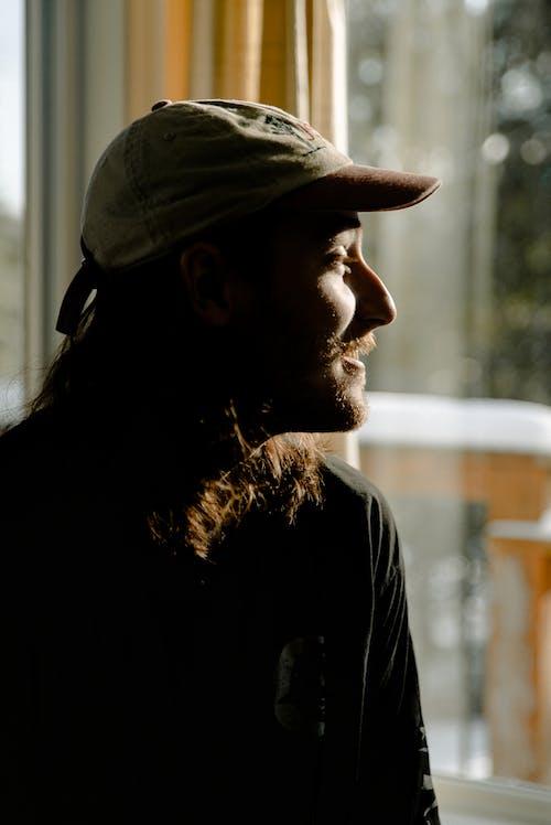 Man Wearing Cap Near Window