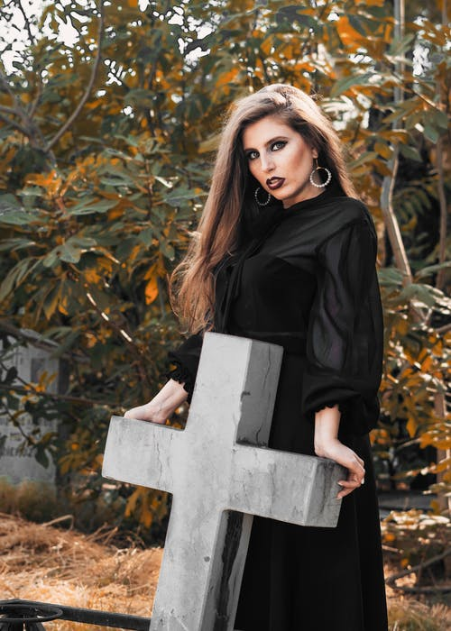 Confident woman in black dress standing in cemetery
