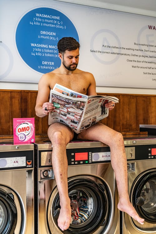 Man Sitting on Front-load Clothes Washer