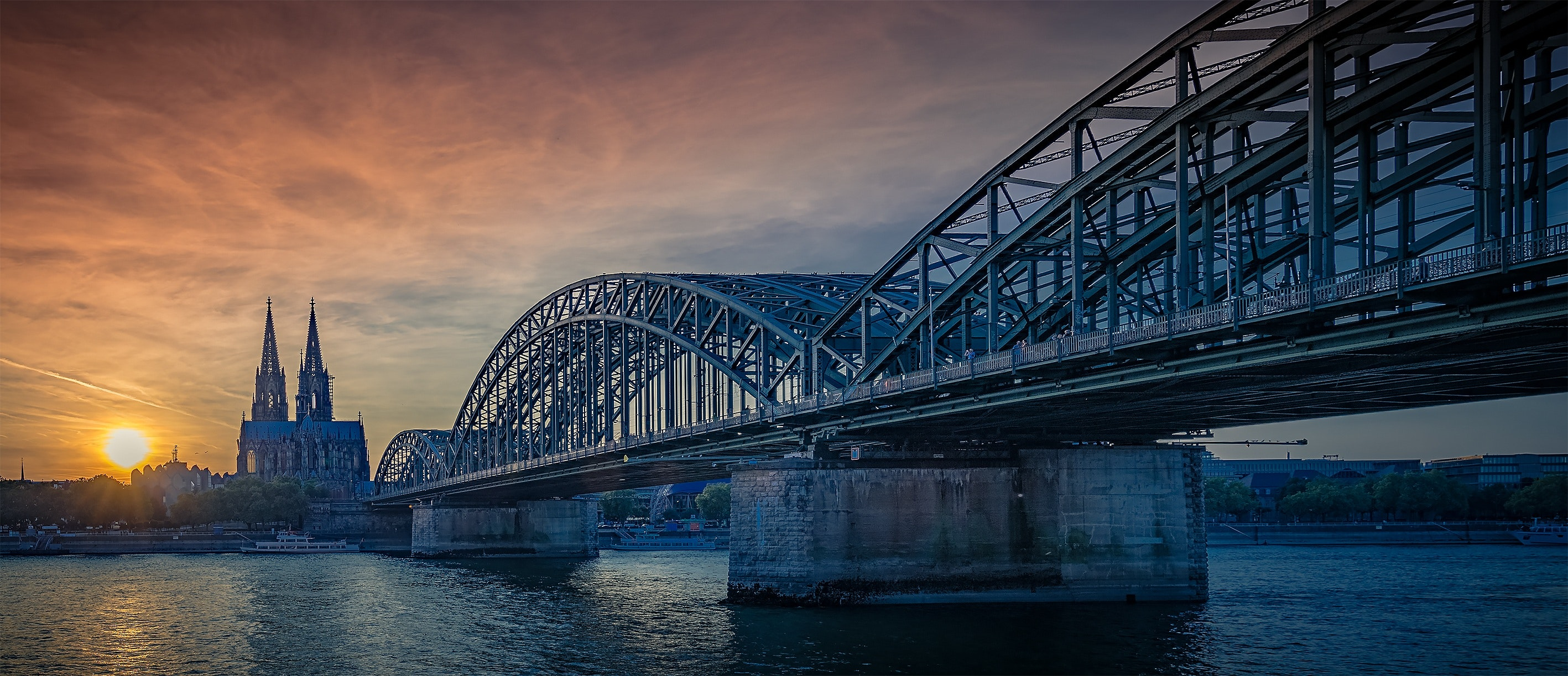 grey concrete bridge on body of water under blue and white sky during daytime  u00b7 free stock photo