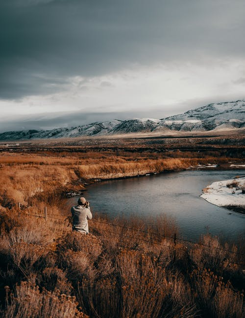 Man in Front of Body of Water Under Cloudy Sky