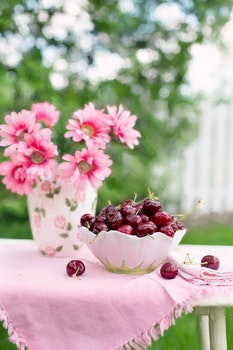 Pink Petaled Flower Beside White and Green Bowl Full of Cherry