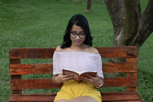 Woman Reading Book While Sitting on Wooden Bench