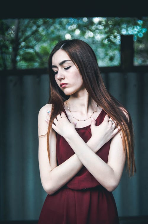Woman Wearing Maroon Dress With Both Hands on Chest While Closing Eyes Standing Near Wall