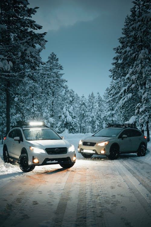 Two White Suvs on Snow-covered Road