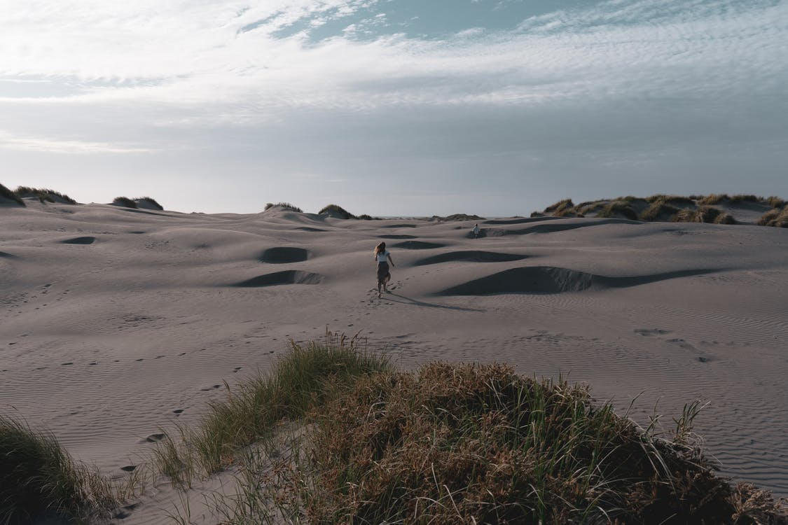Person Walking on Gray Sand