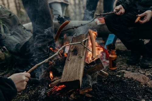 Selective Focus Photography of People Holding Sticks With Sausages