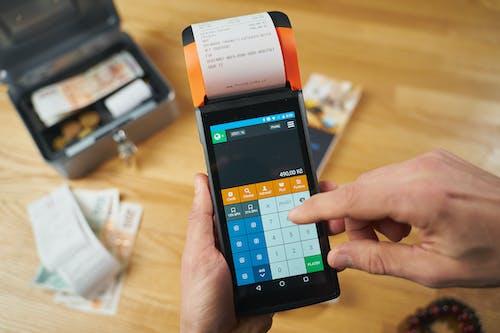 Person Holding Black and Orange Smartphone