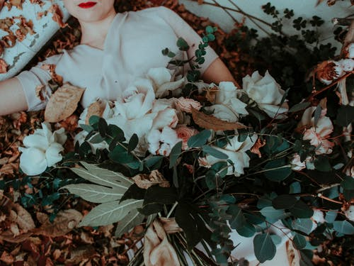 Person Lying on Dried Leaves While Holding White Roses