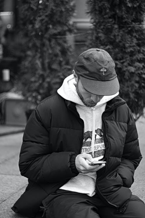 Monochrome Photo of Man Using His Cellphone