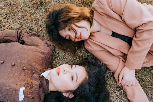 Photo of Women Lying Down on Grass